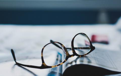 Image of a pair of reading glasses on an open book