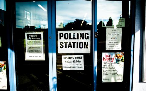Image of a glass door with a Polling Station sign.