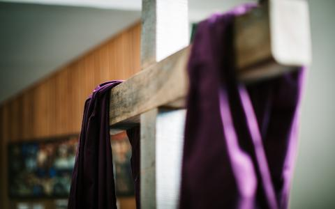 Image of a plain wooden cross with purple material draped over it