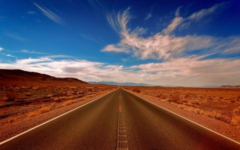 Image of a road stretching in front, deep blue sky, light clouds