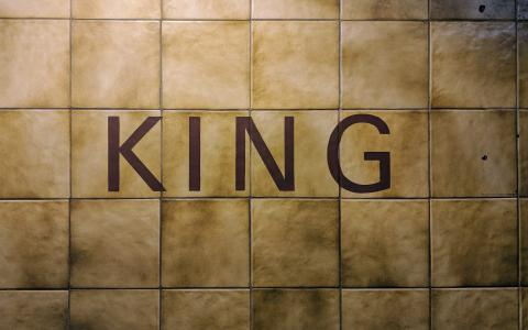 Image of a tiled wall with the word KING in capitals