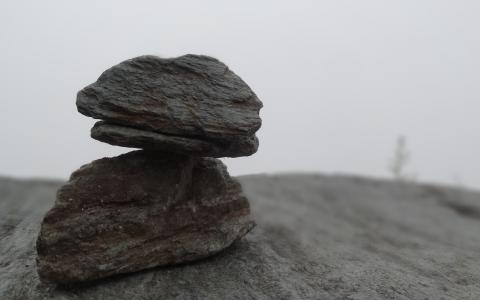 Image of two rocks balanced one on another in mist