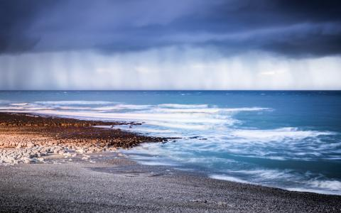 Image of a shingle beach and wild sky