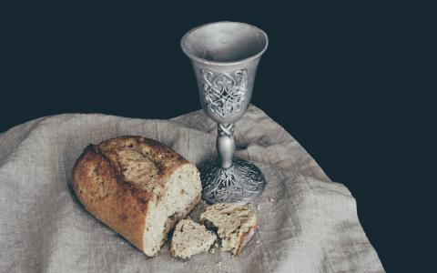 Image of a broken loaf of bread and a cup of wine