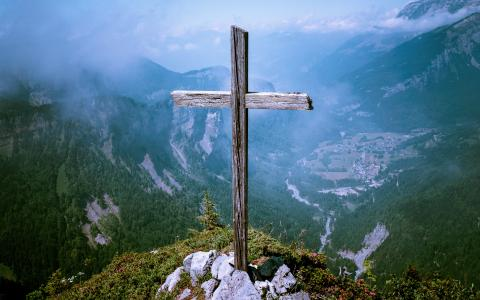 Image of a wooden cross on top of a mountain.