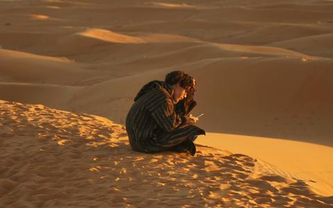 Image of a man sitting on a sand dune
