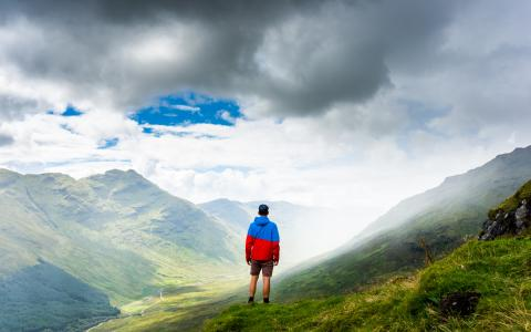 Image of a person standing on a hillside looking at sky and mountains